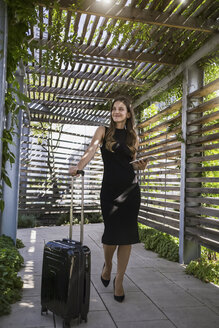 Smiling businesswoman with mini tablet and wheeled luggage - RIBF000315