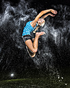 Young woman jumping in the air in between cloud of flour - STSF000888