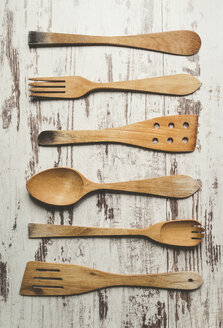Row of six different wooden kitchen utensils on wooden background - RAEF000446