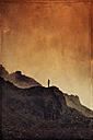 Italy, Lombardy, Alps, Man on rock spur, red sky, textured effect - DWIF000599