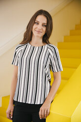 Portrait of smiling young woman standing on yellow stairs - MFF002102