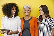 Three smiling women standing in front of a yellow wall - MFF002111