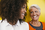Two smiling women in front of a yellow wall - MFF002114