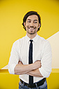 Portrait of smiling mature man wearing shirt and tie standing in front of a yellow wall - MFF002138