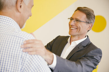 Portrait of smiling mature man talking to another man in an office - MFF002120