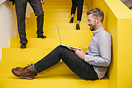 Smiling mature man sitting on yellow stairs with his laptop - MFF002123