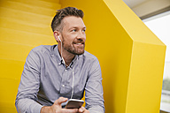Portrait of smiling mature man hearing music with smartphone and earphones sitting on yellow stairs - MFF002126