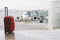 Red suitcase at airport, airplane in background - GEMF000358
