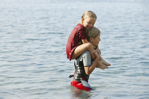 Spain, Mallorca, boy carring little sister on his shoulders in the sea - TMF000036