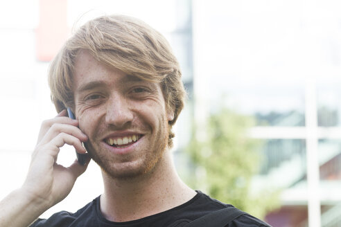 Portrait of smiling young man telephoning with smartphone - SGF001870