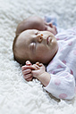 Portrait of sleeping newborn baby girl lying besides her twin brother - SHKF000361