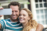 Smiling couple taking a selfie outdoors - FMKF002095