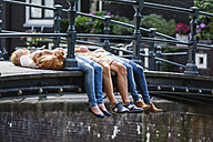 Netherlands, Amsterdam, three friends lying on bridge - FMKF002100