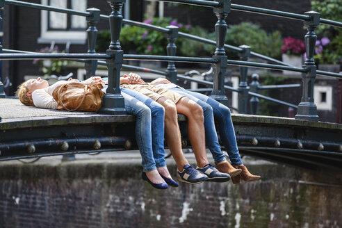 Netherlands, Amsterdam, three friends lying on bridge - FMKF002100