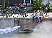 Netherlands, Amsterdam, three happy friends sitting with drinks at town canal - FMKF002108