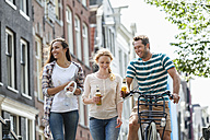 Netherlands, Amsterdam, happy friends with beer bottles and bicycle in the city - FMKF002111