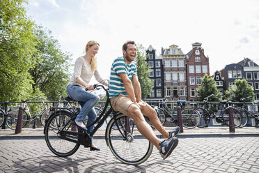 Netherlands, Amsterdam, happy couple riding bicycle in the city - FMKF002089
