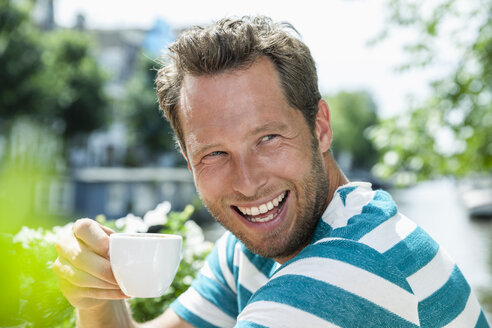 Netherlands, Amsterdam, happy man drinking cup of coffee at an outdoor cafe - FMKF002119