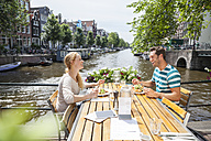 Netherlands, Amsterdam, happy couple having lunch at town canal - FMKF002124