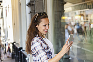 Netherlands, Amsterdam, smiling young woman in the city looking at cell phone - FMKF002135