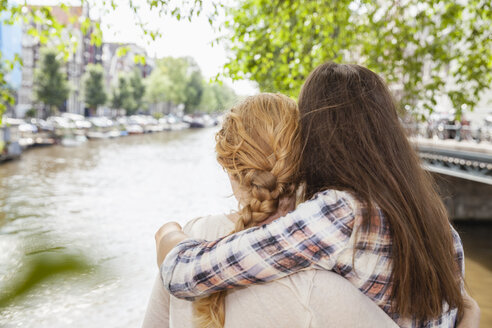 Netherlands, Amsterdam, two women embracing at town canal - FMKF002138