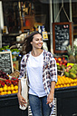 Smiling young woman at greengrocer's shop - FMKF002141