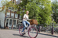Netherlands, Amsterdam, woman riding bicycle  in the city - FMKF002144