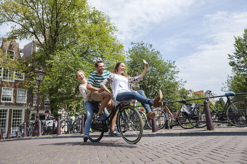 Netherlands, Amsterdam, three playful friends riding on one bicycle in the city - FMKF002147