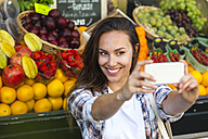 Smiling young woman taking a selfie at greengrocer's shop - FMKF002150