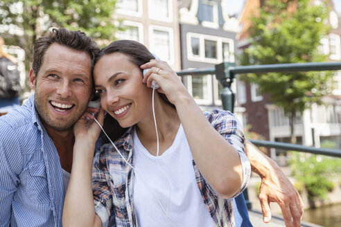 Netherlands, Amsterdam, happy couple sharring headphones outdoors - FMKF002156