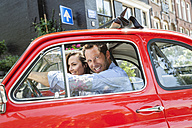 Netherlands, Amsterdam, happy couple with small car in the city - FMKF002159