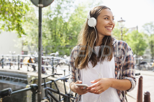Netherlands, Amsterdam, happy young woman with headphones - FMKF002164