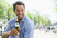Netherlands, Amsterdam, happy man drinking beer from bottle - FMKF002167