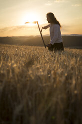 Organic farmer with scythe in barley field at sunrise - MIDF000602