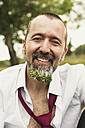 Portrait of smiling businessman with plant in his beard - MIDF000609
