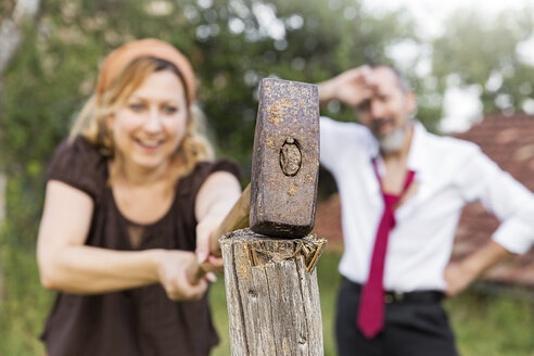 Woman hitting fence post with sledgehammer with exhausted businessman in the background - MIDF000616