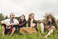 Businessman having a break on the countryside with three villagers - MIDF000618