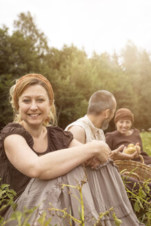 Smiling woman and two other people sitting on potato field - MIDF000628