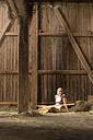 Farmwoman sitting with hay fork in barn - MIDF000635