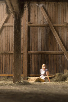 Farmwoman sitting with hay fork in barn - MIDF000635