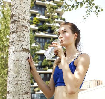 Young woman in sportswear taking a break, drinking water - PASF000030