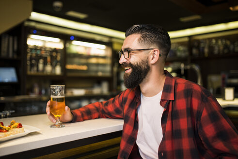 Hipster with glass of beer and tapas sitting at counter in a pub - JASF000110