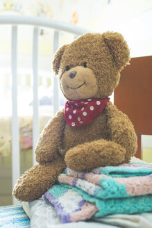 Stack of blankets and a teddy-bear on a chair - DEGF000522