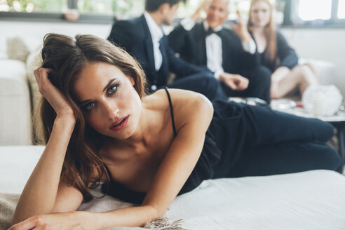 Beautiful woman lying on couch, party guests in background - CHAF001556