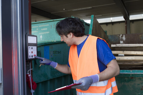 Worker at a waste container operating machine - SGF001864