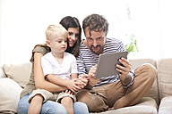 Parents and little son sitting on the couch with digital tablet - MFRF000455
