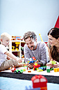 Parents playing with their little son on the carpet of children's room - MFRF000410