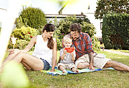 Parents sitting with their little son on a blanket in the garden - MFRF000432