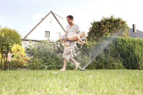 Father and his little son having fun together in the garden - MFRF000450