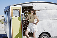 South Africa, Cape Town, young woman standing in front of a caravan - RORF000124